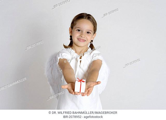 Girl dressed up as a Christmas angel with a gift, Christmas