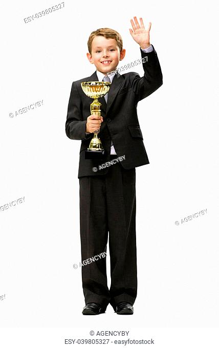 Full-length portrait of little businessman keeping golden cup and waving hand, isolated on white. Concept of leadership and success