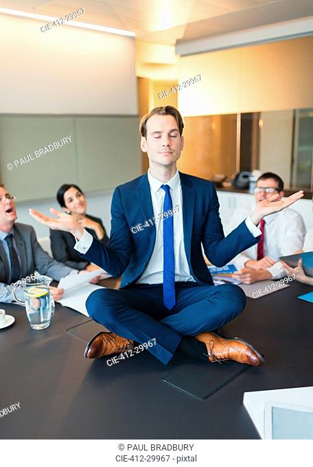 Colleagues watching zen-like businessman meditating in lotus position on conference table