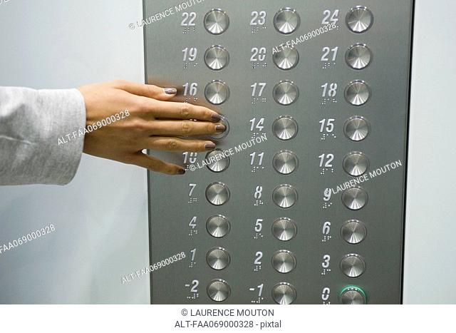 Woman's hand pressing elevator button, cropped