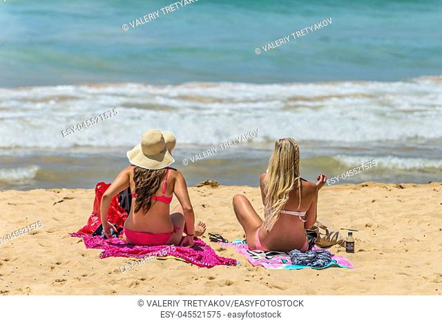 Manly, Australia - November 9, 2014: Ladies by the shore in Manly Beach in Manly, Australia. Seven miles from the heart of Sydney