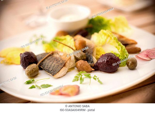 Plate of fish with salad and olives