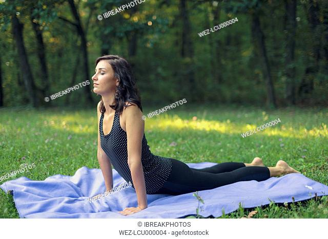 Croatia, Woman practicing yoga in cobra pose, yoga in nature