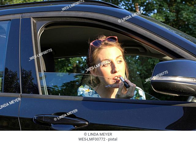 Young woman sitting in car, applying lipstick
