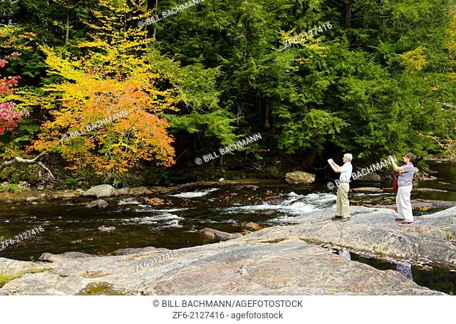 Waterville Vermont tourist taking pictures on falls under covered bridge Montgomery Covered Bridge with fall foliage in Northern New England 2