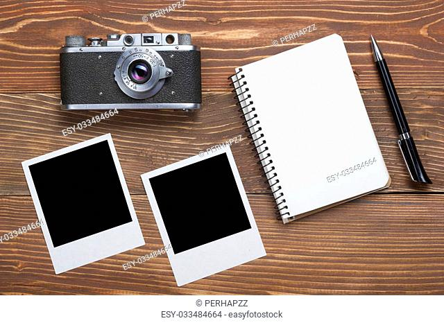 Travel, vacation concept. Camera, notepad, pen and photography on office wooden desk table. Top view with copy space for text