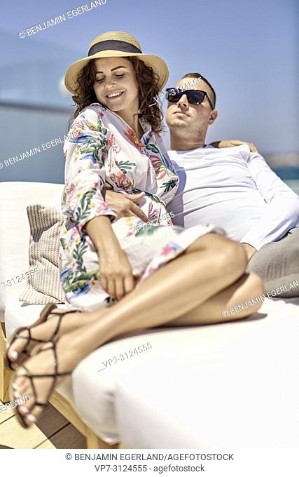 couple relaxing on sunbeds, holiday, love, togetherness