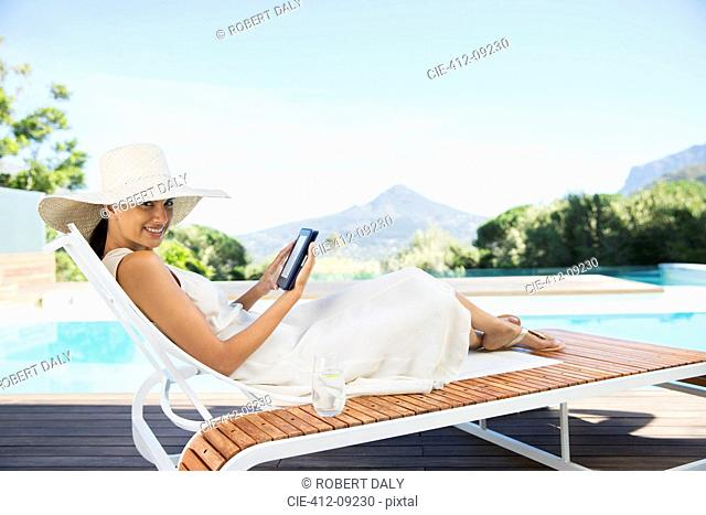 Woman using digital tablet on lounge chair at poolside