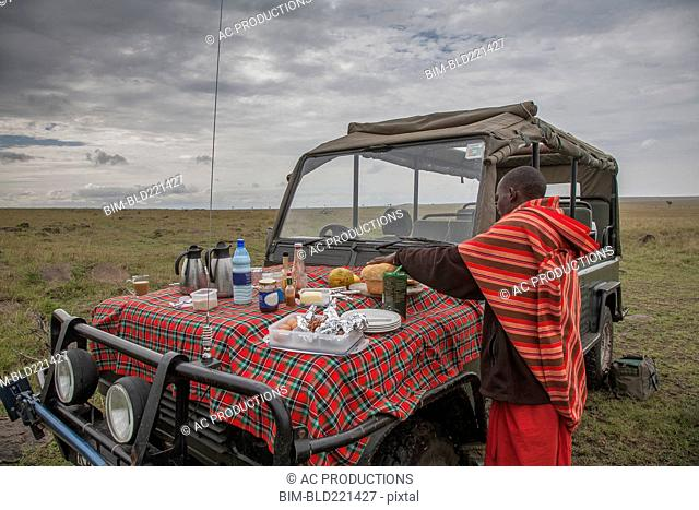 Black man having picnic on hood of car in remote field