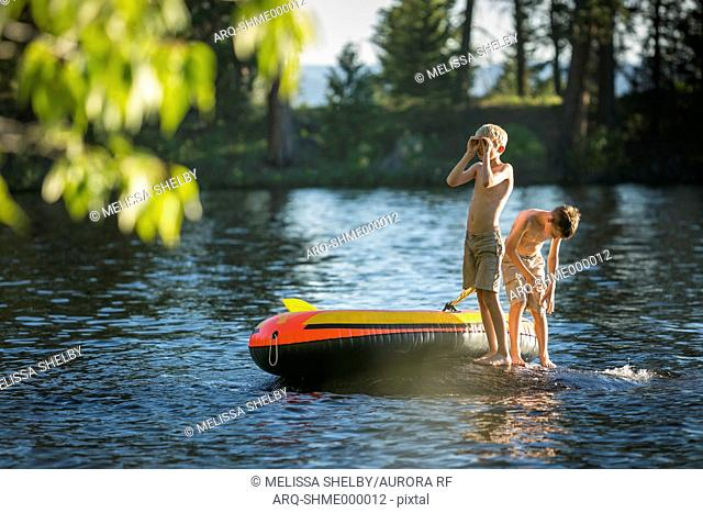 Two Boys swimming and playing on an inflatable raft in Duck Bay on Payette Lake in McCall, Idaho