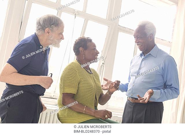 Older people laughing near window