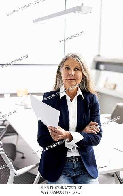 Senior businessswoman holding documents in conference room