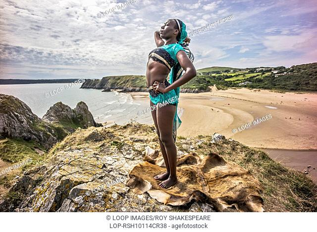 An afro caribbean woman relaxing on hills overlooking Three Clffs Bay on the Gower