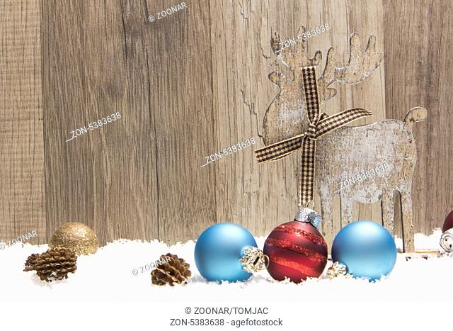 christmas decoration with wood background, snow, elk, christmas baubles gold, blue and red and pine cones