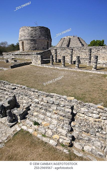 View to the Templo Redondo-Round Temple and visitors standing at the top of the Castle of Kukulcan-Castillo de Kukulcan in Mayapan Archaeological site, Merida