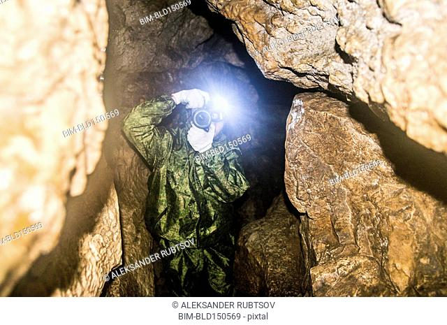 Caucasian man taking photograph in rock formation cave