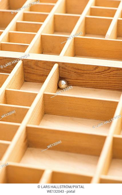 Small steel ball in wooden box with empty compartments. Conceptual image of loneliness, solitude and being trapped