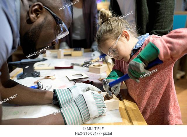 Scientist helping girl with hammer and wood in science center workshop