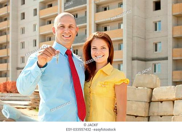 Outdoor portrait of happy couple against real estate