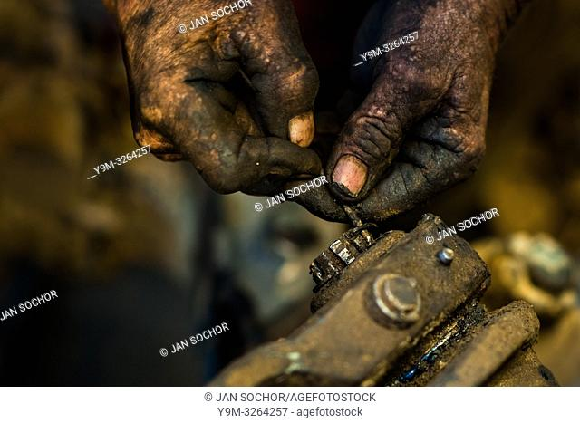 A Colombian car mechanic works on an axle while performing maintenance on a truck in Barrio Triste, Medellín, Colombia, 28 November 2017