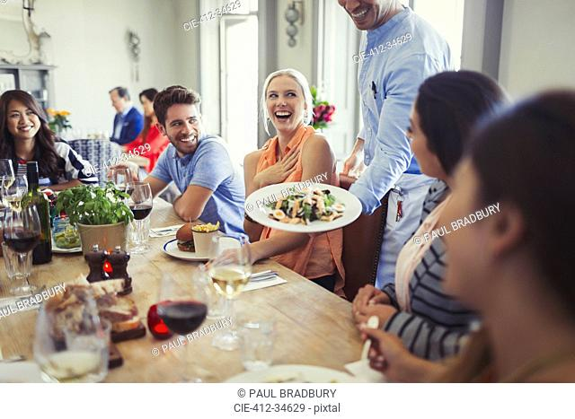 Waiter serving salad to woman dining with friends at restaurant table