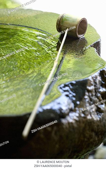 Bamboo ladle on water fountain, close-up