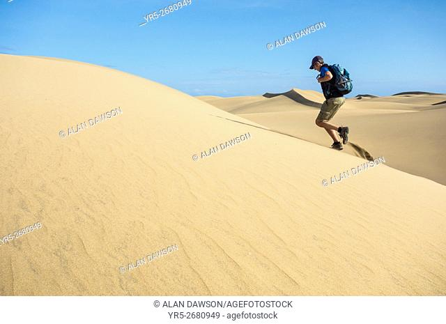 Mature man with backpack running on sand dunes at Maspalomas, Gran Canaria, Canary Islands, Spain