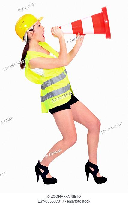 Sexy woman dressed as builder screaming in a traffic cone