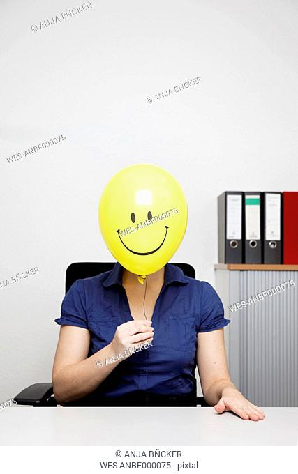 Germany, Businesswoman with smiley face balloon