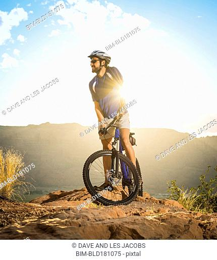 Hispanic man riding bike on remote hilltop