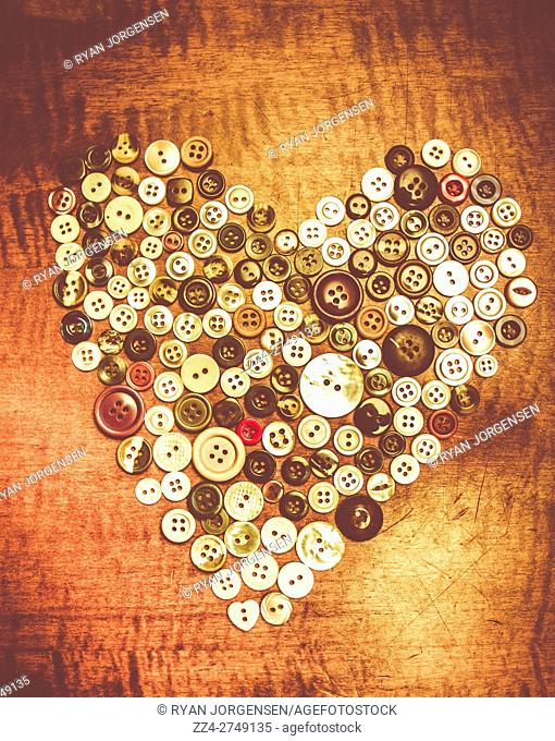 Still life fashion picture of a heart made of colorful used buttons of different size on wooden table. Dressmaking love