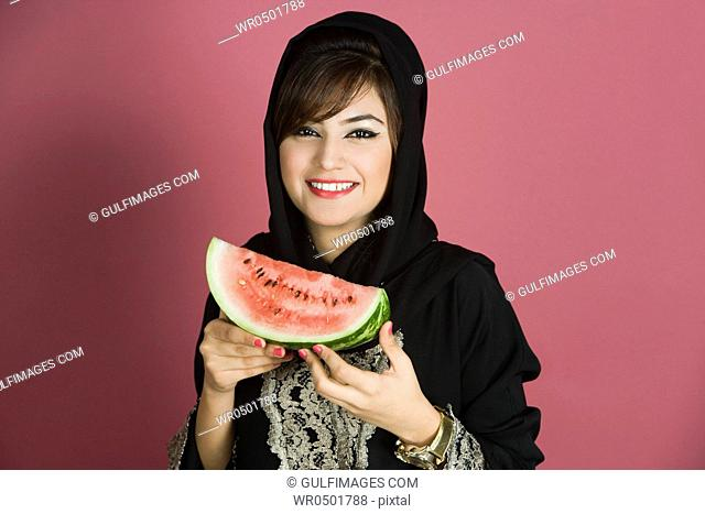 Young woman holding watermelon, portrait