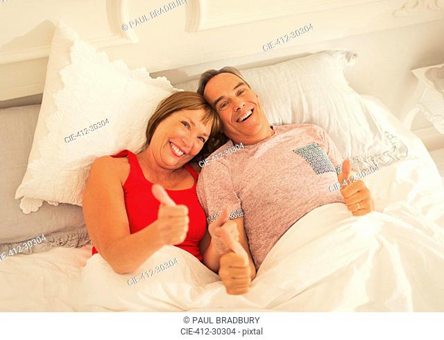 Portrait playful mature couple gesturing thumbs-up in bed