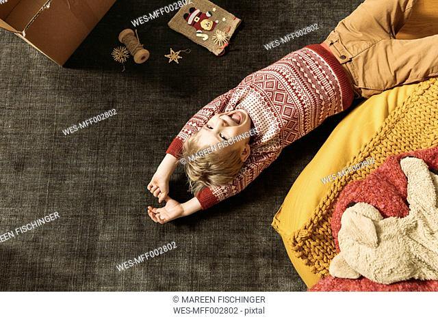 Little boy laughing and playing on the carpet by box of Christmas decoration