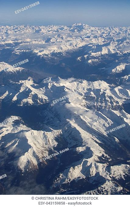 Swiss Alpes with snowy mountain tops aerial view towards the east during afternoon flight in December