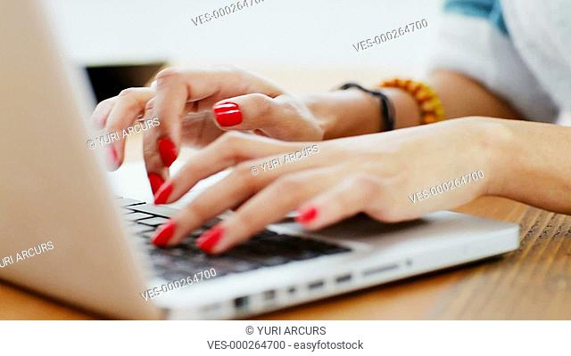 Close up of the hands and face of a pretty young woman using a laptop