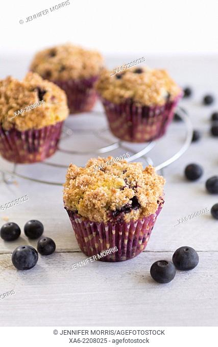 Blueberry streusel muffins in purple paper cases with a few blueberries