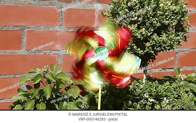 Pinwheel is a simple child's toy made of a wheel of paper or plastic curls attached at its axle to a stick by a pin