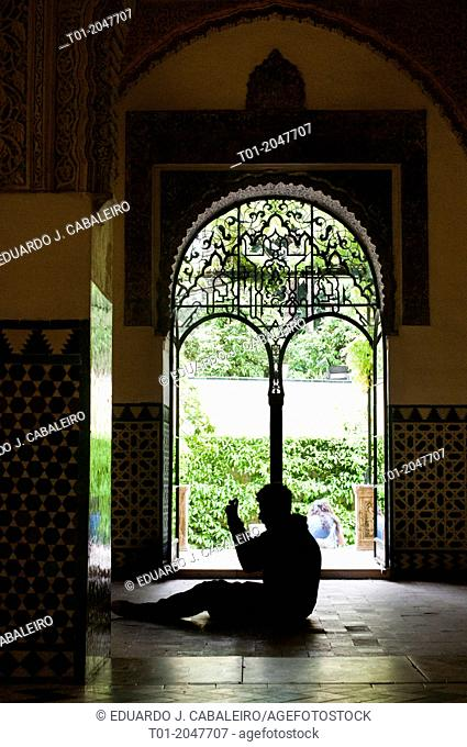 silhouette of man sitting in front of a door. Alcazar of Seville