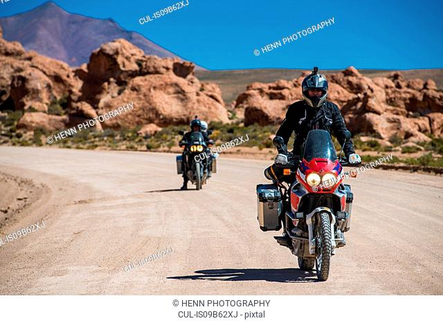 Motorcyclists riding motorcycles on dusty road, Uyuni, Oruro, Bolivia, South America