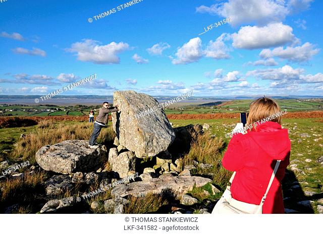 Young women taking a photo of boyfriend pushing stone, King Arthurs Stone, Cefn Bryn, Gower peninsula, south-Wales, Wales, Great Britain