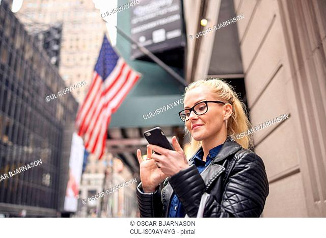 Woman on street reading texts on smartphone, New York, USA