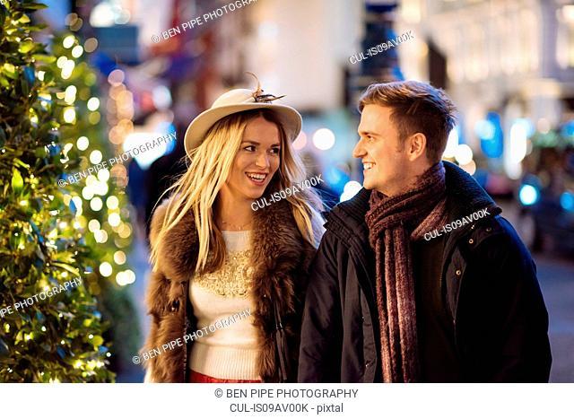 Romantic young couple strolling along New Bond street at xmas, London, UK