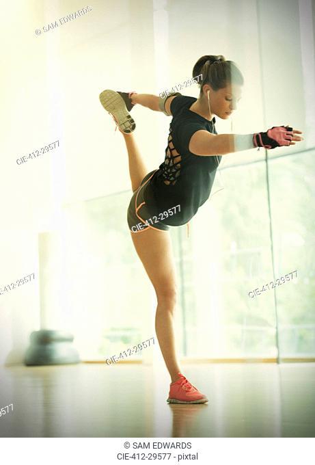 Woman holding king dancer pose in gym studio