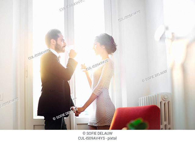 Stylish young couple drinking sparkling wine at window before night out