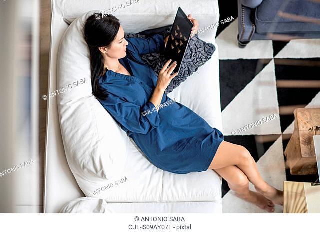 Overhead view of woman reclining on hotel room sofa using digital tablet, Dubai, United Arab Emirates