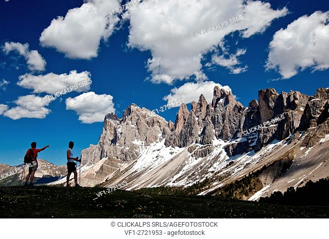 Hiker to Brogler Pass admire the group of Odle of Funes. Dolomites. Trentino Alto Adige. Italy Europe