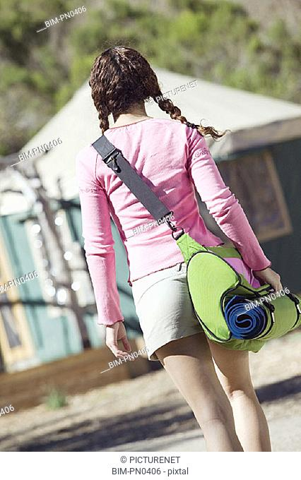 Rear view of woman walking with camping bag