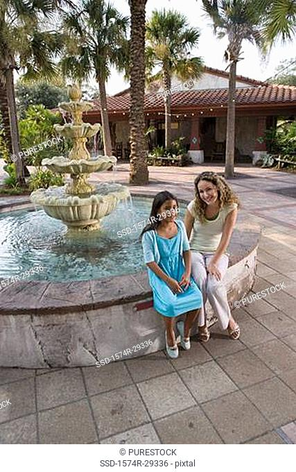 Portrait of mother and daughter sitting together by water fountain