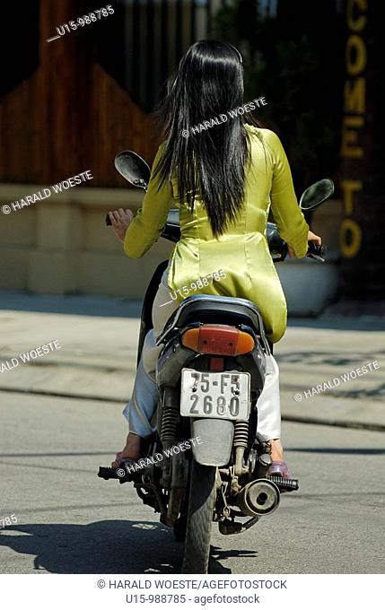 Elegant vietnamese woman riding a motorbike through Hue, Vietnam